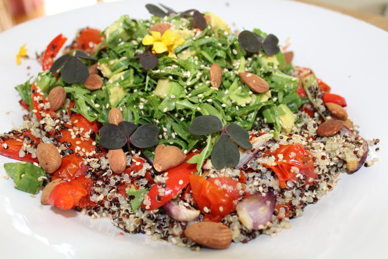 Farvet quinoa med bagte grøntsager, rucolatopping og mandler