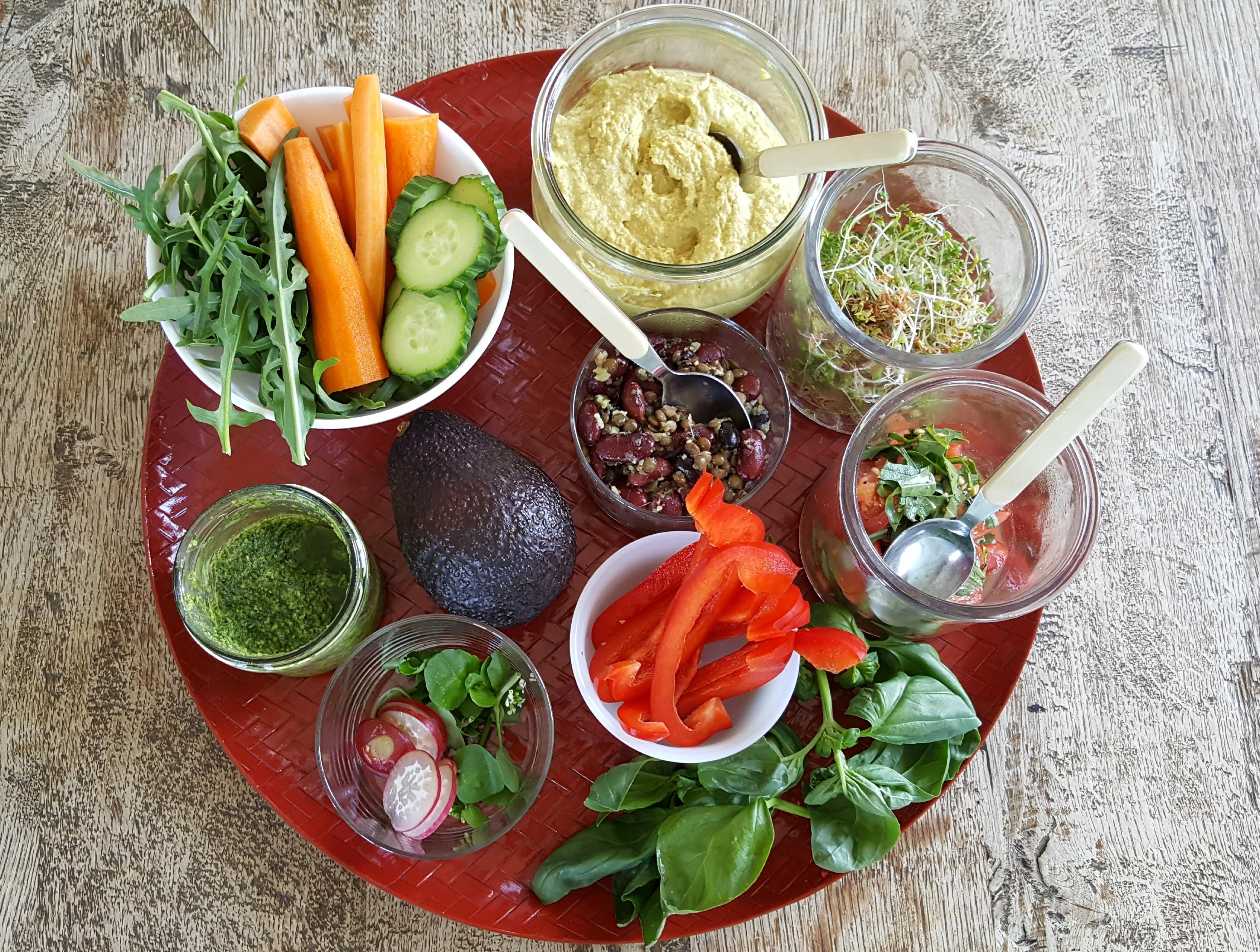 Frokost med hummus, pesto, marinerede bønner og forskelligt grønt tilbehør